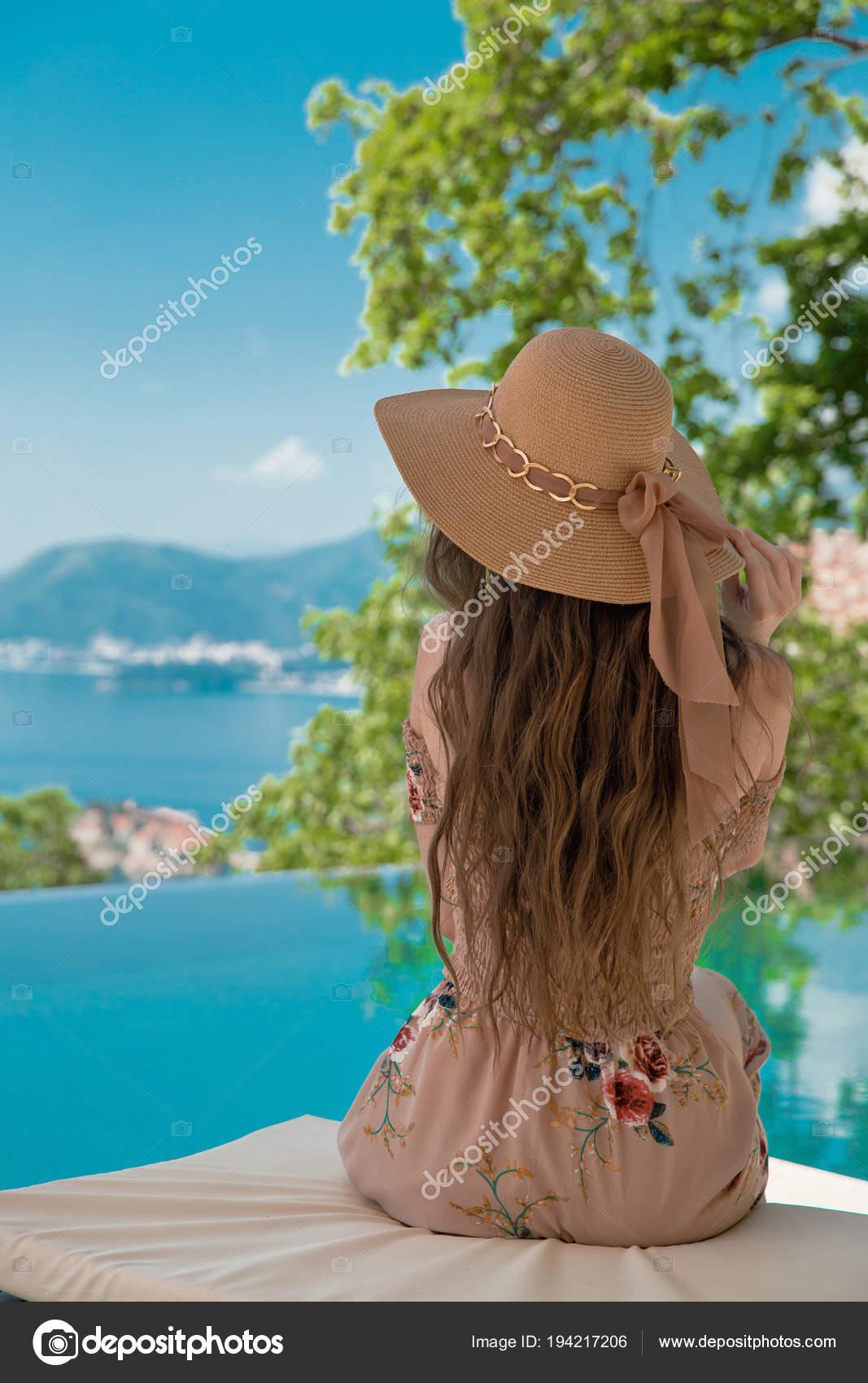 9971735578 Linda mulher moda chapéu de praia, desfrutando a vista para o mar pela  piscina sobre luxury resort tropical. Paraíso exótico. Viagens, turismo e  conceito de ...