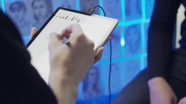 Mladý muž kreslí portrét pomocí tabletu a elektronického pera, zpomalený pohyb, mělká hloubka pole