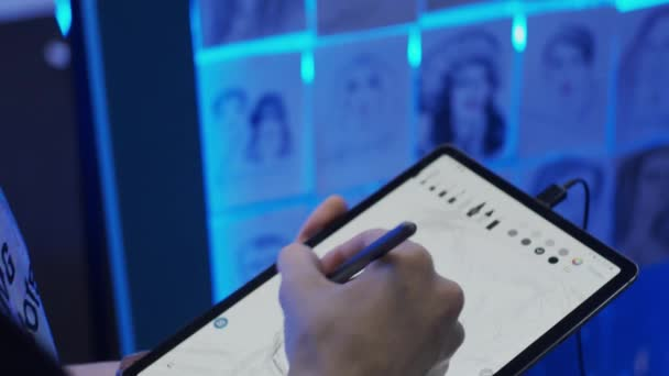 Young man drawing portrait using tablet and electronic pen, slow motion, shallow depth of field