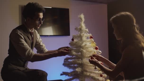 Young man and woman decorating christmas tree, slow motion