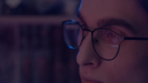 Young man in glasses working at computer, reflection of monitor in glasses, slow motion, shallow depth of field