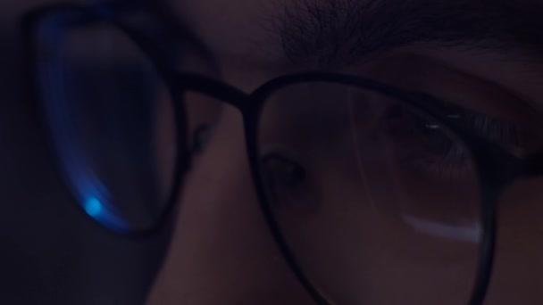 Fiatal férfi szemüvegben dolgozik a számítógép, tükröződik a monitor szemüvegben, lassított felvétel, sekély mélysége mező