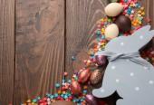 Složení s čokoládová velikonoční vejce, barevné sypání a zajíček hračka na dřevěné pozadí