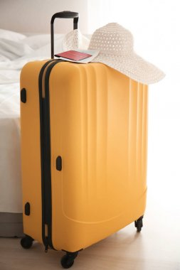 Large suitcase, hat and documents indoors