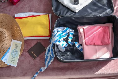 Tourist's stuff with open travel suitcase on bed