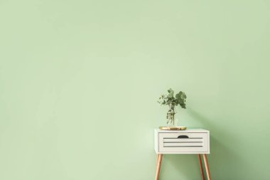 Stylish table with eucalyptus branches in vase on color background