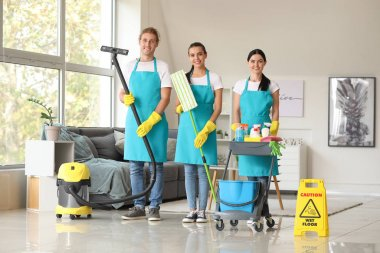 Team of janitors with cleaning supplies in room