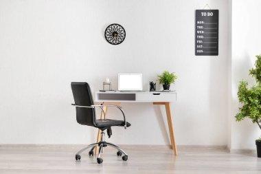 Stylish workplace near white wall