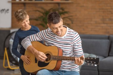 Father and his little son with guitar at home