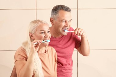 Mature couple brushing teeth on color background