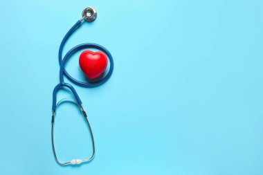 Modern stethoscope and red heart on color background
