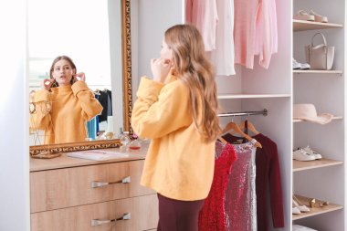 Beautiful young woman choosing accessories in her dressing room
