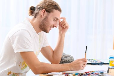 Young male artist working in studio