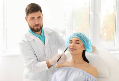 Plastic surgeon applying marks on patient's face in clinic