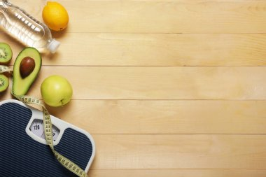 Different healthy food with measuring tape and scales on wooden background. Diet concept
