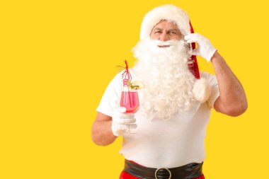 Santa Claus with cocktail talking by phone on color background. Concept of vacation