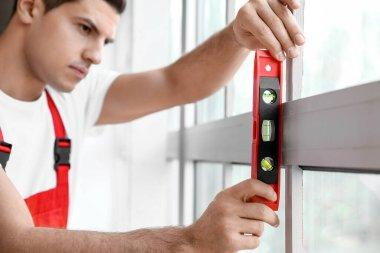 Male worker installing window in flat