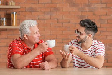 Young man and his father drinking tea in kitchen
