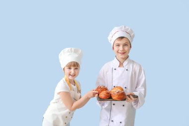 Cute little chefs with pastry on color background