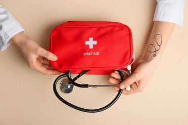 Hands of doctor with stethoscope and first aid kit on color background
