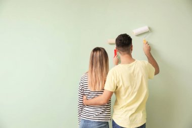 Happy young couple painting wall in their new house
