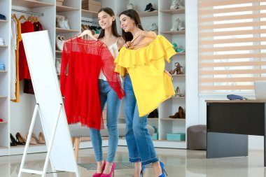 Young women choosing clothes in modern store