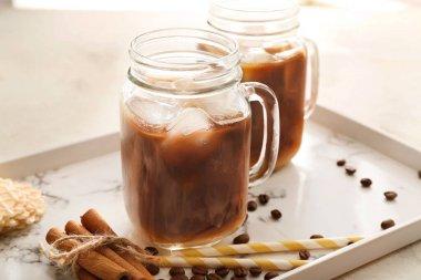 Mason jars of tasty cold coffee on tray