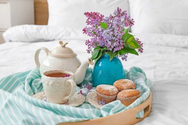Vase with beautiful lilac flowers, tea and muffins on tray in bedroom