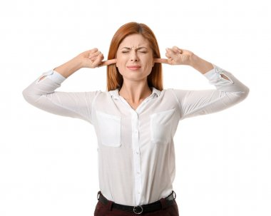Young woman suffering from loud noise on white background