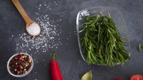Čerstvý rozmarýn s kořením, zeleninou a olejem na tmavém pozadí