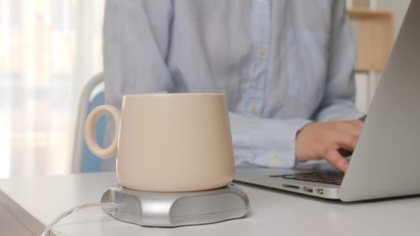 Šálek kávy s ohřívačem na stole mladé ženy pracující s notebookem v kanceláři