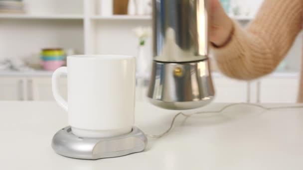 Žena nalévání horká káva forma hrnce do šálku s ohřívačem na stole doma