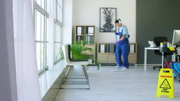 Männlich asiatisch hausmeister hören musik während wischen floor im büro