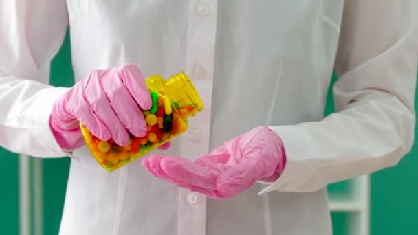 Doctor with bottle of colorful pills, closeup