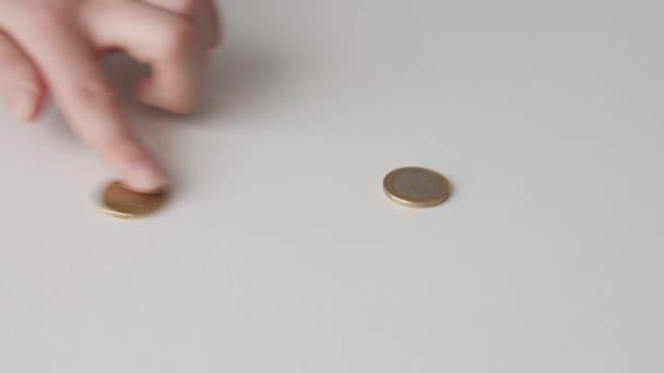 Žena počítá mince na bílém stole. Pojem dluhu