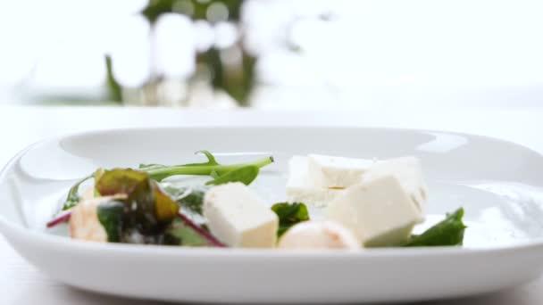 Kousky chutného sýra Feta padající na talíř, detailní záběr