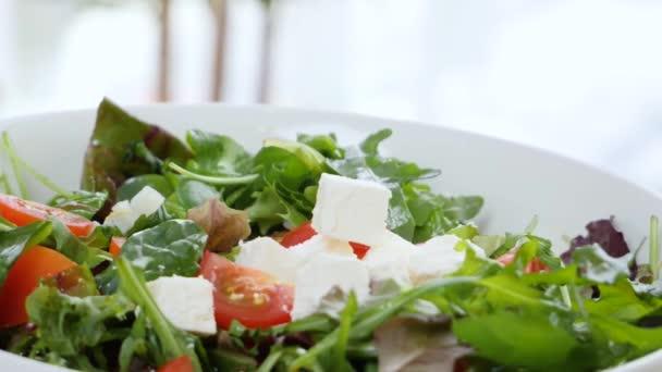 Kousky chutného sýra Feta padající do mísy se zeleninovým salátem, detailní záběr