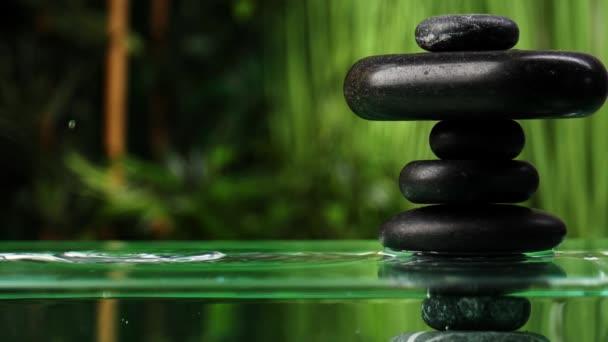Voda kapající do jezera s hromadou zenových kamenů v orientální zahradě