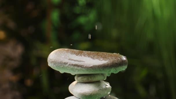Voda kapající na hromadu zenových kamenů v orientální zahradě