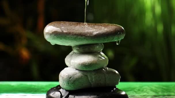 Voda tekoucí na hromadu zenových kamenů v orientální zahradě