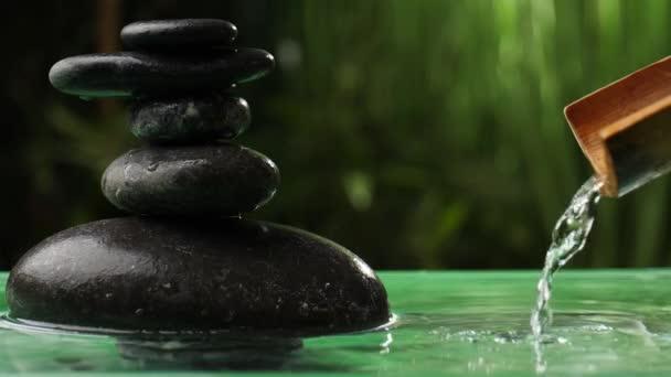 Voda tekoucí z bambusu do jezera s hromadou zenových kamenů v orientální zahradě