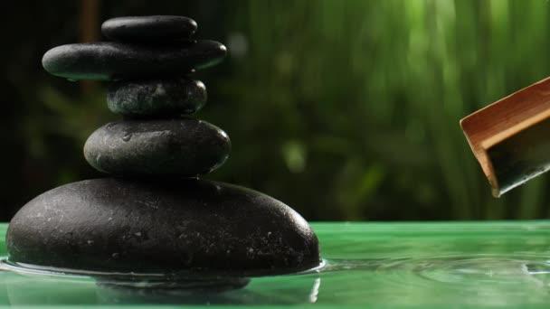 Voda kapající z bambusu do jezera s hromadou zenových kamenů v orientální zahradě