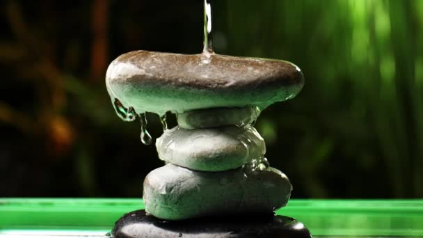Water pouring on stack of zen stones in oriental garden
