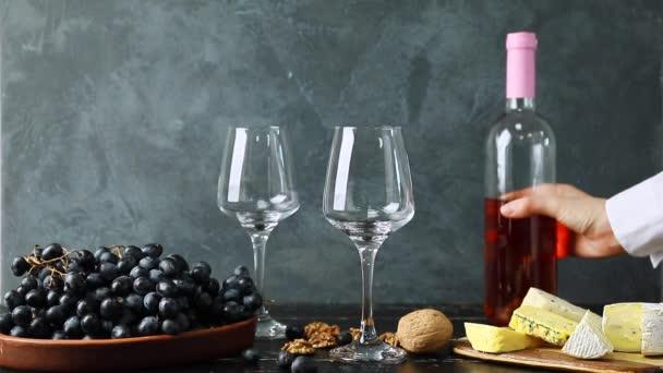 Frau gießt leckeren Wein aus Flasche in Gläser auf Tisch