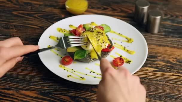 Žena jíst chutné vejce Benedikt u stolu, detailní záběr