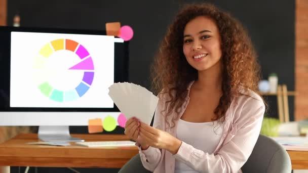 Glückliche afroamerikanische Designerin mit Farbpalette im Büro