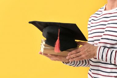 Young man with graduation hat and books on color background