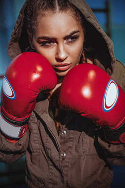 Young female boxer ready to fight in leather boxing gloves. Sexy fitness happy blonde girl in sport wear with perfect body in boxing gym posing in boxing ring. Sport, fitness, lifestyle concept