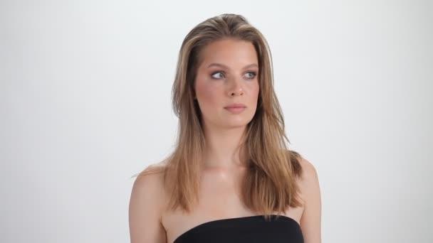 Gyönyörű modell pózol fehér háttérrel. Egy lány pózol a kamera előtt. Fiatal nő profil portré. Női személy tökéletes bőrrel