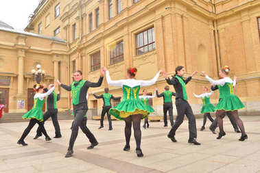 Group of people in national costumes are dancing Irish dances.